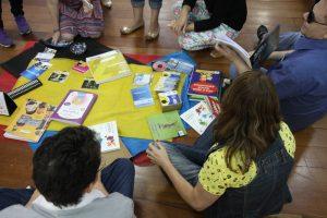 Descrição de imagem: Diversas pessoas estão sentadas em roda. No centro, há uma toalha preta estendida no chão com diversos livros dispostos.