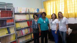 Descrição de imagem: Célia posa para foto ao lado de três integrantes da associação. Ao fundo há uma estante com livros.