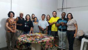 Descrição de imagem: Foto de 10 pessoas em pé, homens e mulheres, posando para uma foto. Eles estão atrás de uma mesa com livros e audiolivros do projeto Leitura Digital Acessível.