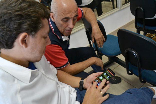 Descrição da imagem: foto de um homem manuseando um celular. Outro homem ao lado dele observa o aparelho.