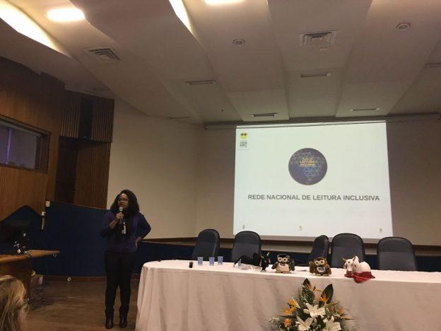 Descrição da imagem: foto de uma mulher falando ao microfone. Atrás dela, um telão com o logotipo da Rede Nacional de Leitura Inclusiva.