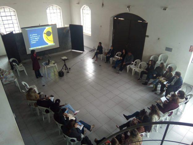 Descrição da imagem: foto de um grupo de 20 pessoas sentadas em um semicírculo. À frente deles há uma mulher de pé e um telão com o logotipo da Fundação Dorina.