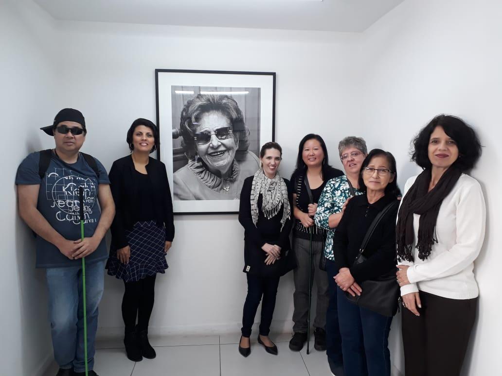 Descrição da imagem: foto de sete pessoas de pé, olhando pra frente e sorrindo. Duas delas seguram bengalas. Na parede atrás deles há um retrato em preto e branco de Dorina Nowill sorrindo.