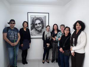 Descrição de imagem: Foto de um grupo de sete pessoas na entrada da Fundação Dorina. Ao fundo, está um quadro de D.Dorina em preto e branco. À esquerda do quadro, está um homem de óculos escuros e com uma bengala verde, e uma mulher de roupas pretas. À direita do quadro, estão outras cinco mulheres. Todos sorriem.