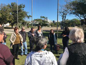 Descrição de imagem: Cerca de dez pessoas estão de pé, em roda em um parque. Elas sorriem e conversam.
