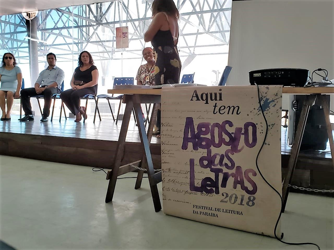 """Descrição da imagem: foto de quatro pessoas sentadas, olhando para uma mulher de pé. Ao lado direito há uma mesa com um cartaz escrito """"Aqui tem Agosto das Letras 2018 - Festival de Leitura da Paraíba"""""""
