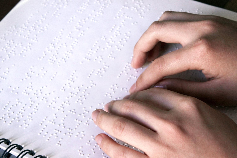 Descrição de imagem: foto de duas mãos sobre uma página em braille.