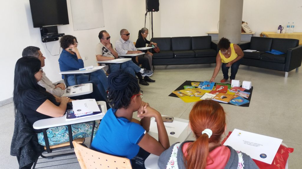 Descrição da imagem: Foto da metade de uma roda com 8 pessoas sentadas. Ao centro, está estendido no chão um pano preto com dezenas de livros em tinta braille dispostos. Perla está agachada e pega um livro que está no tapete.