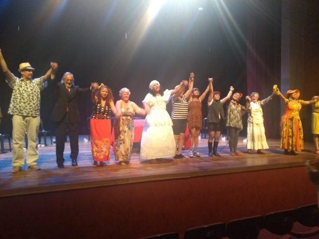 Descrição da imagem: foto de 11 pessoas perfiladas, de mãos dadas e braços pra cima. Elas estão num palco.