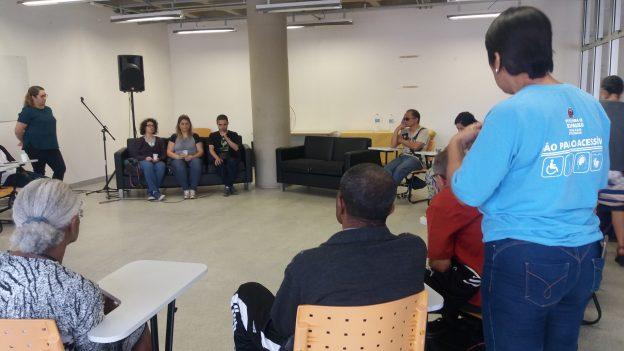 Descrição da imagem: foto de pessoas sentadas em roda. Duas delas estão de pé.