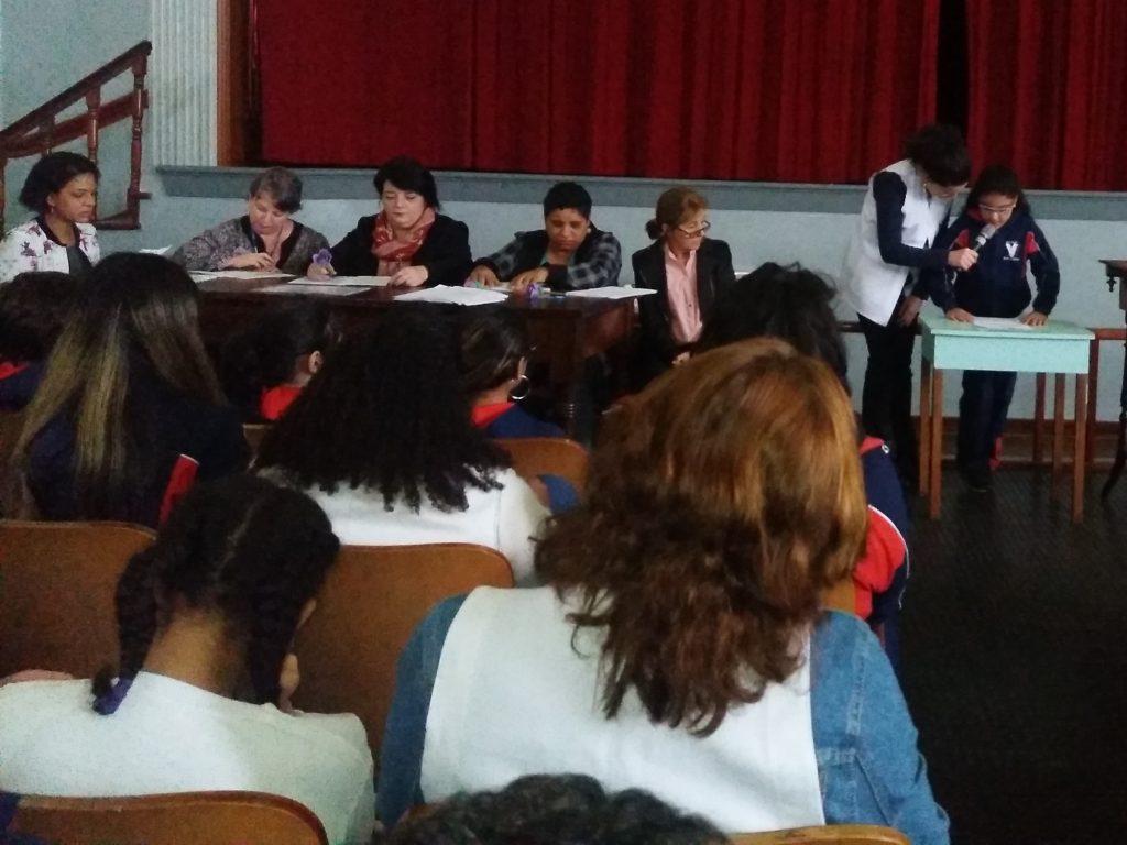 Descrição de imagem: Foto de um auditório. À esquerda, estão cerca de dez crianças sentadas na plateia, de costas para a foto. À frente delas, há uma mesa com cinco professoras sentadas. Elas seguram canetas e papéis. Uma delas está lendo uma folha em Braille. À direita da imagem, está uma menina em pé em frente a uma mesa. Ela lê uma folha de papel e uma professora está ao lado dela segurando um microfone.