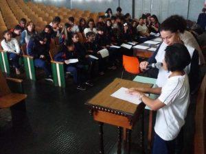 Descrição da imagem: foto de mulher segurando microfone na altura da boca de uma moça que tateia papel em branco. À frente delas há um grupo de pessoas sentadas em cadeiras universitárias.