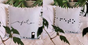 A foto mostra à esquerda uma almofada cinza onde está escrita a palavra afeto na cor preta. Na parte inferior há um pequeno pedaço de tecido retangular preto sobre a almofada e um botão de cerâmica pregado por cima. Do lado direito há outra almofada na cor cinza com a palavra afeto escrita em braille na cor preta. As duas almofadas são arrematadas nas bordas por bolinhas de lã branca e estão sobre tecidos brancos com folhagens verdes em volta.