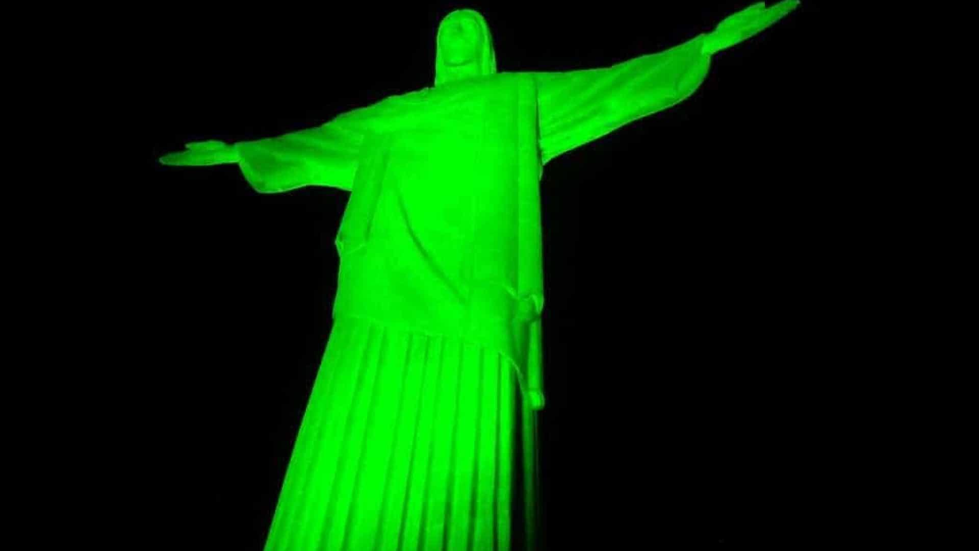 Descrição da imagem: foto do Cristo Redentor iluminado na cor verde.