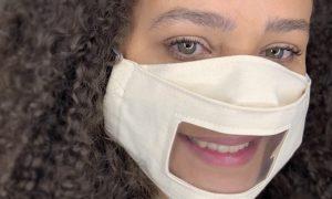 Foto do rosto de uma mulher de pele e olhos claros, cabelos longos e enrolados, que tem no rosto um máscara de proteção com espaço transparente na região da boca. A mulher está sorrindo e olhando para a câmera. Crédito: Divulgação.
