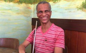 Homem negro sorridente, de camiseta listada em dois tons de rosa, está sentado num banco com encosto de madeira escura e segura uma bengala de metal à frente do corpo. O fundo mostra imagem com vários tons coloridos.