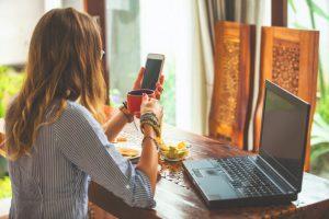 Mulher de costas sentada de frente a uma mesa com computador, tigela de frutas e prato com comida usa o celular enquanto toma uma xícara de café; no fundo, cortinas são iluminadas pelo sol
