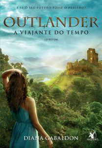 Imagem de uma mulher de cabelos castanhos compridos, usando vestido sem mangas, parada de costas com o bralo esquerdo sobre a cabeça, olhando para as ruínas de um castelo ao fundo, à direita, sobre uma montanha coberta de vegetação exuberante.